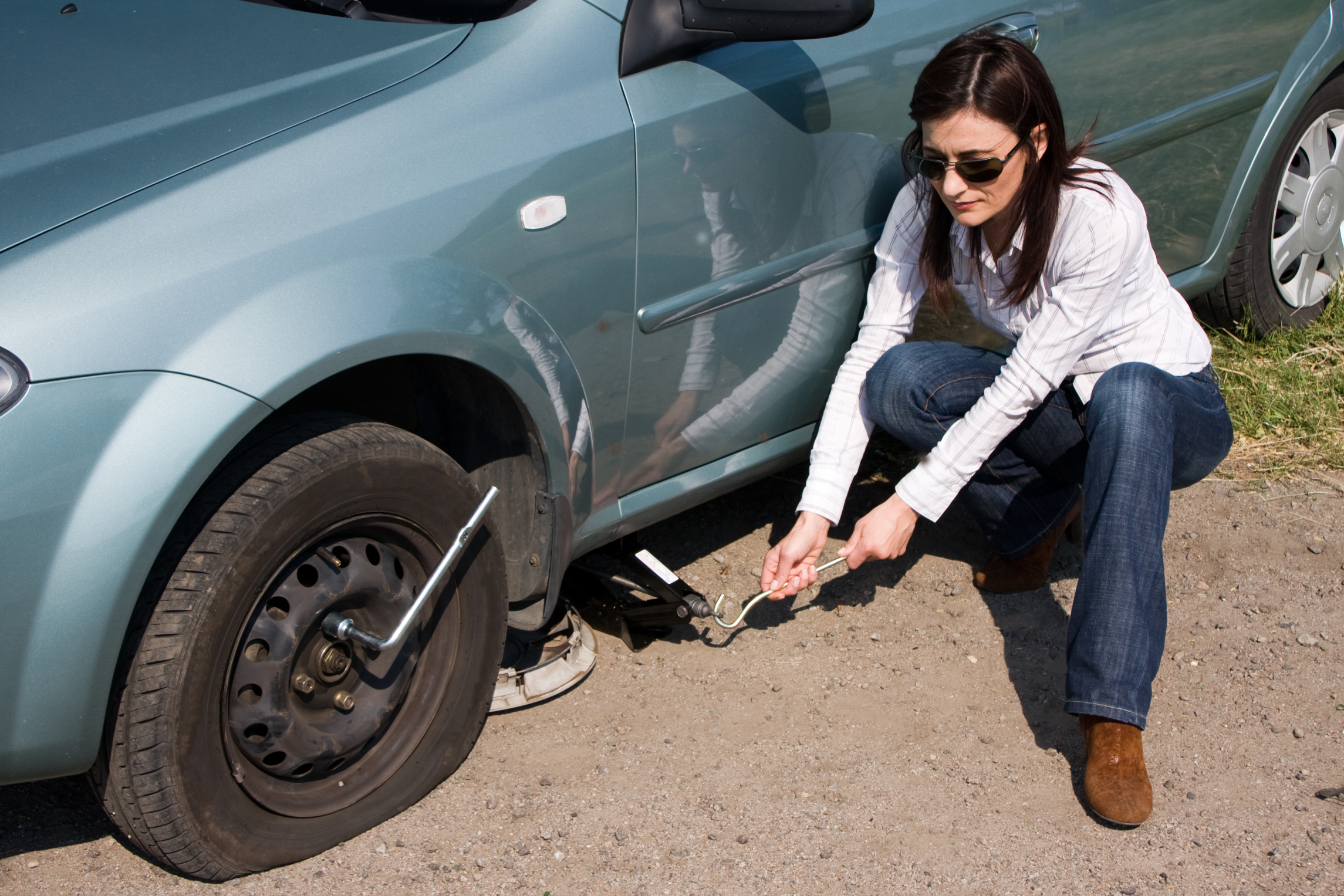 woman changing tire - Basic Car Tips